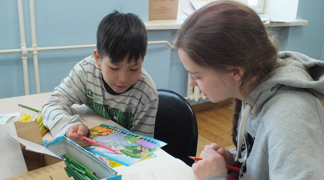 A young child reads to a Projects Abroad volunteer working with children in Mongolia at a local school.